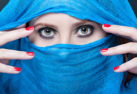 Fashion beauty portrait of model with smokey makeup posing with blue scarf