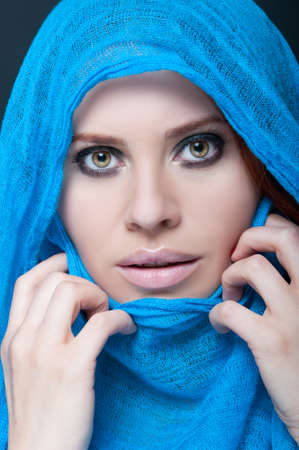 Beautiful and exotic young woman with blue burka on her head in closeup