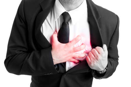 heartsick: Businessman holding his heart in pain in black and white picture as heart attact or palpitation concept Stock Photo