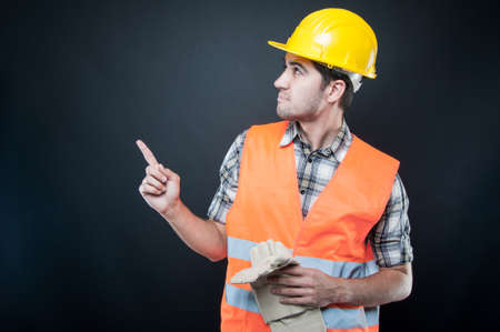Side view of handsome constructor wearing equipment pointing up on black background Stock Photo