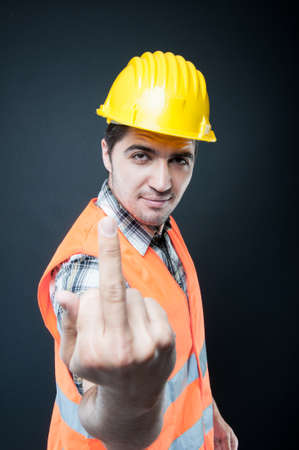 Portrait of constructor showing middle finger gesture on black background Stock Photo