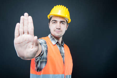Constructor wearing equipment showing stop gesture on black background with copypsace advertising area Standard-Bild