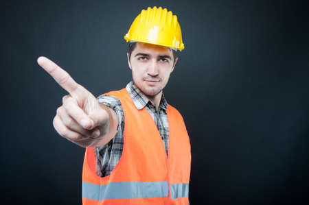 Constructor wearing equipment showing denial gesture on black background with copypsace advertising area