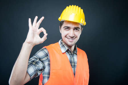 Constructor wearing equipment showing okay gesture and smiling  on black background with copypsace advertising area