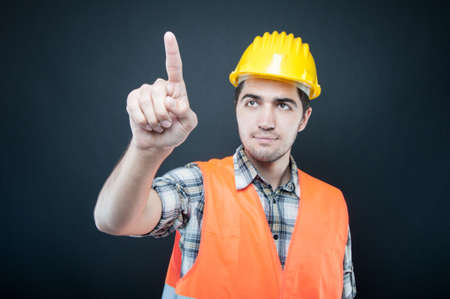 Portrait of constructor wearing equipment using invisible touch screen on black background Stock Photo