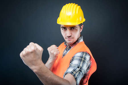 Constructor wearing equipment showing both fists like fighting on black background