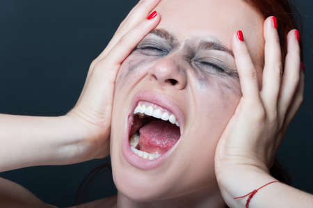 Frustrated woman with smeared mascara screaming out loud with rage