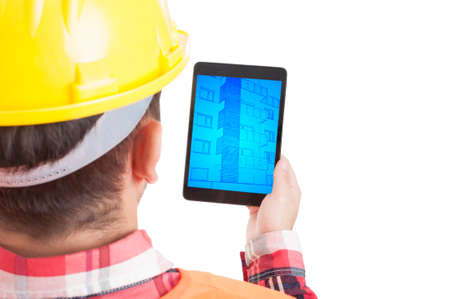 Rear view of male constructor holding tablet with building plan on white background