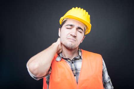 Portrait of constructor holding back neck like hurting on black background