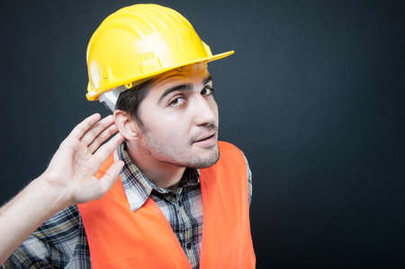 Constructor wearing equipment showing cant hear gesture on black background with copypsace advertising area