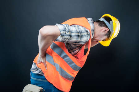 Constructor wearing equipment holding his back and bending over like hurting on black background Stock Photo