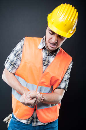 Portrait of constructor wearing hard hat and reflecting vest holding his wrist like hurting on black background