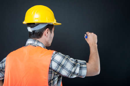 Back view of constructor wearing equipment writing with blue marker on black background