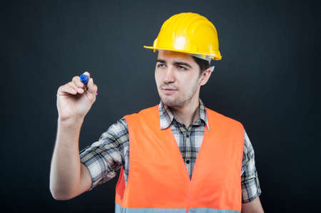 Constructor wearing equipment writing or drawing with blue marker on black background Stock Photo