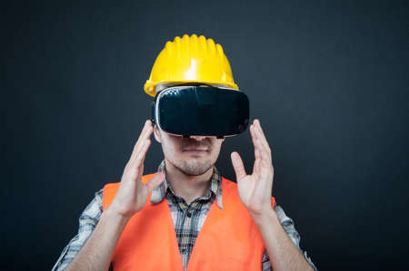 Constructor portrait wearing virtual reality goggles on black background with copypsace advertising area Banque d'images