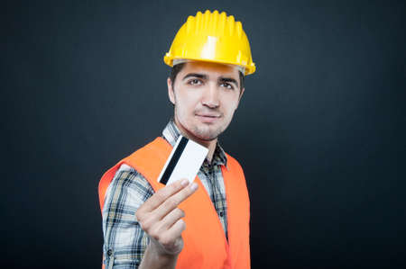 Constructor wearing equipment showing credit or debit card on black background