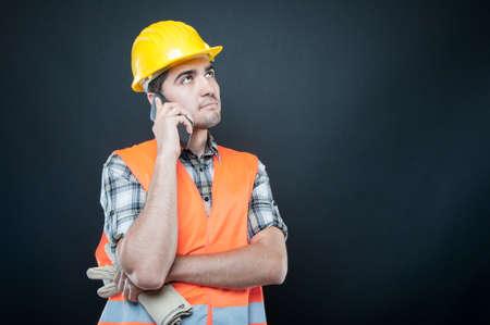 Constructor tragen Ausrüstung sprechen am Telefon mit Handschuhen auf schwarzem Hintergrund mit Copypsace-Werbefläche
