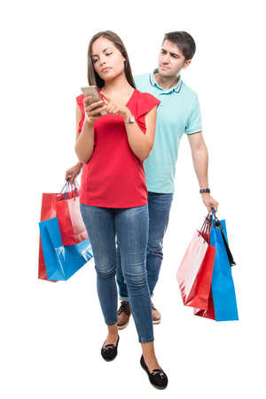 Full body of couple carrying lots of shopping bags and texting on phone isolated on white background