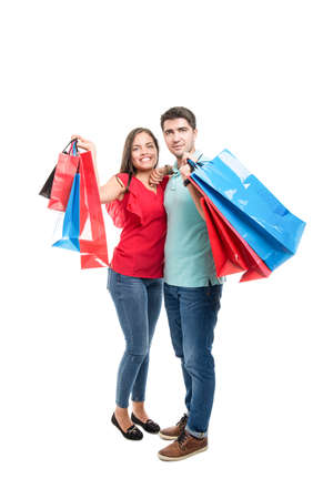 Full body of attractive couple smiling carrying shopping bags isolated on white background Stock Photo