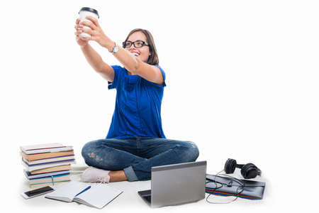 Student girl smiling holding coffee around books laptop phone and headphone isolated on white background Stock Photo