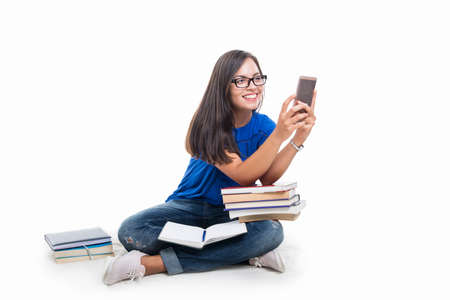 Student girl sitting taking picture with smartphone  with books around isolated on white background