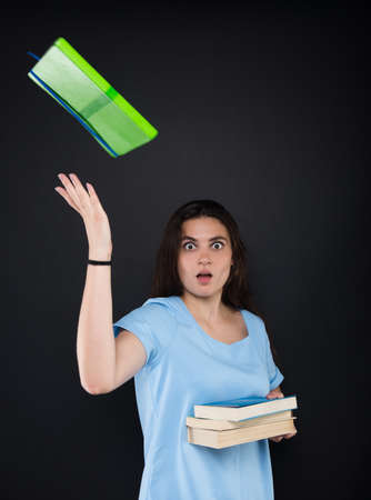 Young female student preparing for exams and throwing books in the air