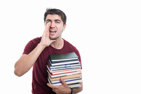 Handsome student holding pile of books and yelling isolated on white background with copypsace advertising area Banco de Imagens - 86411978