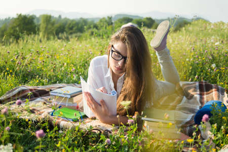 Gril lying on the grass and writing on notebook in a warm sunny day