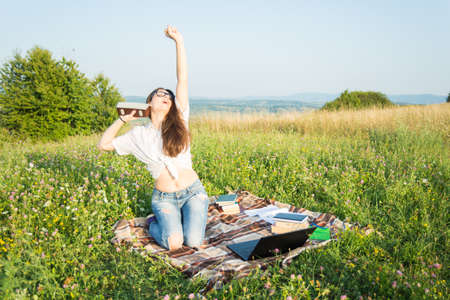 Girl enjoy listening music and reading books while having fun on grass field