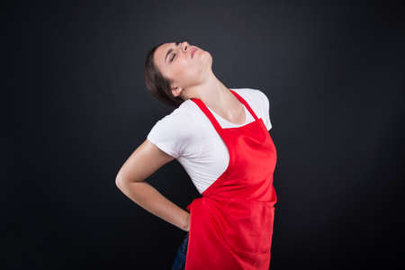 Female seller with lower back pain having an exhausted day at work isolated on dark background