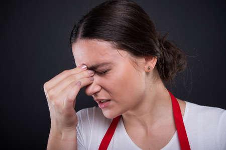 Closeup view of stressed female seller having headache or migraine