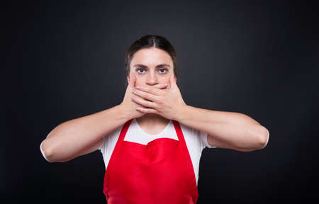 Young female employee covering closed mouth with hands or doing speak no evil gesture Stock Photo