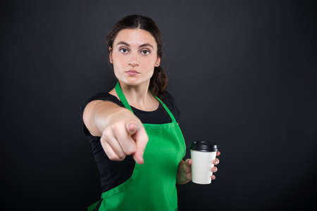 bebes lindos: La empleada de sexo femenino seria con el café le indica en fondo oscuro