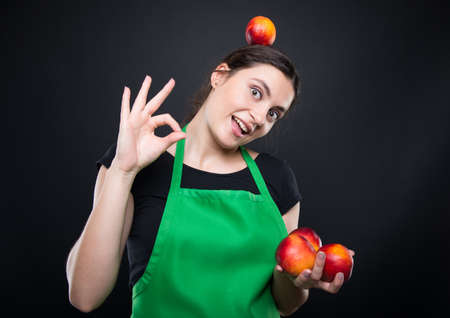 Cheerful young seller holding many nectarines and promoting a healthy lifestyle