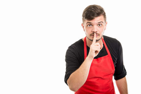 Male supermarket employer showing silence gesture  with index finger isolated on white background with copyspace advertising area