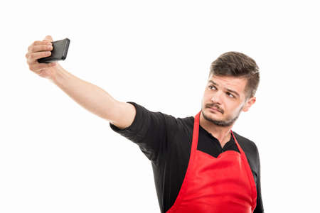 Male supermarket employer taking selfie with smartphone isolated on white background Stock Photo