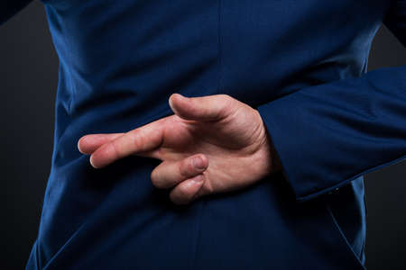 Closeup view of liar businessman standing with crossed fingers behind his back Foto de archivo
