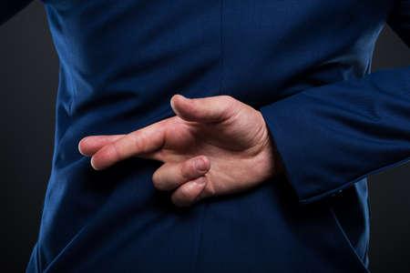 Vue rapprochée de l'homme d'affaires menteur debout avec les doigts croisés derrière le dos Banque d'images - 90948589