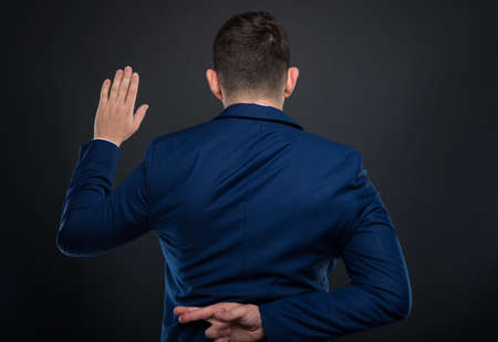Man in business suit holding crossed fingers behind his back and taking a fake promise