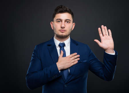 Businessman holds his hand on his chest and taking a solemn vow