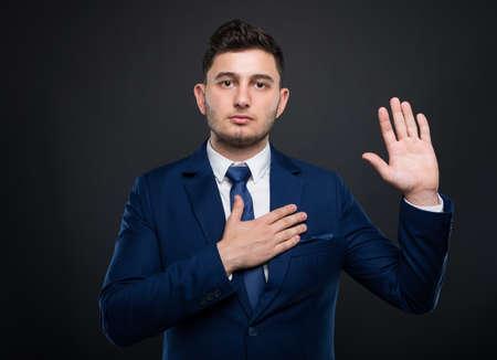 De zakenman houdt zijn hand op zijn borst en legt een plechtige gelofte af