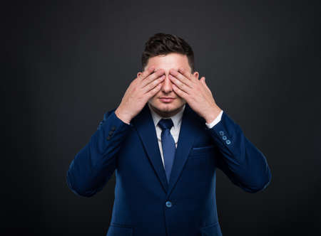 Business man in suit closes his eyes with hands. See no evil concept