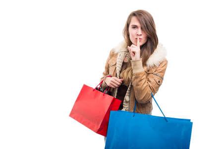 Stylish shopping girl indicate silence gesture with finger on lips isolated on white background