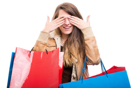 Happy female hipster covering her eyes as see no evil concept while doing shopping