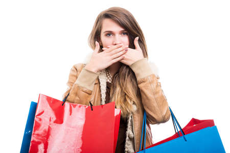 Girl at shopping doing speak no evil gesture and carrying colorful bags