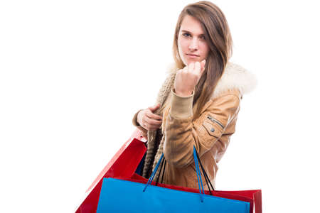 Angry young shopper showing her fist while carrying paper bags on white background Stock Photo