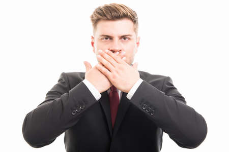 Handsome business man covering mouth like mute gesture isolated on white background