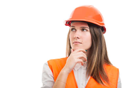 Portrait of pensive female construction or engineer wearing hardhat and looking up