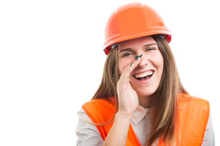 Woman builder in protection uniform keeps hand on mouth and screams on white background Stock Photo