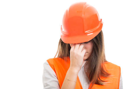 Engineer girl with hardhat got headache and feeling very tired on white background
